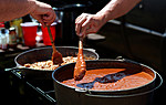 Hands of John Adkins, left, and Steve Ishibishi of Briefcase Chili, stir up a fresh batch of chili d